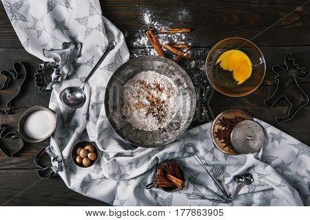 Ingredients for making ginger cookies over scorched dark wooden background, top view, horizontal composition