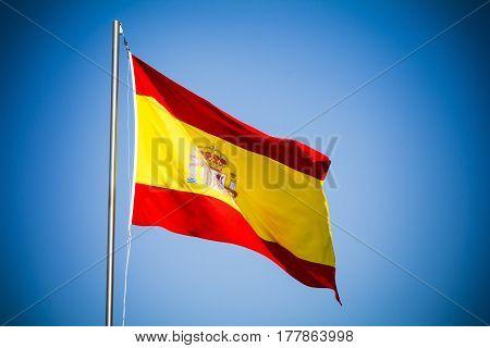Spain flag fluttering against blue sky on sunny day