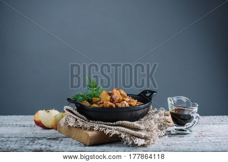 Homemade roasted chicken with apples served with fresh dill in black iron pan, grey wall background, selective focus, copy space, horizontal composition