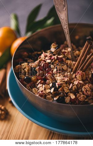 Ingredients for making oat cookies with berries and cinnamon sticks in metal bowl, selective focus, vertical composition