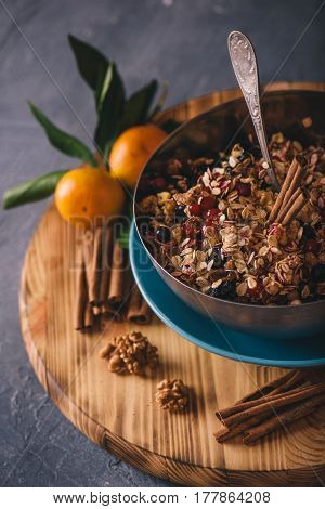 Ingredients for making oat cookies served with fresh mandarins in metal bowl over grey concrete background, selective focus, vertical composition