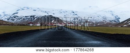 Empty road leading to small town with snowy mountains in background Iceland Winter time