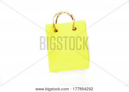 Tiny shopping bag of yellow paper with rope handles. Isolated over white