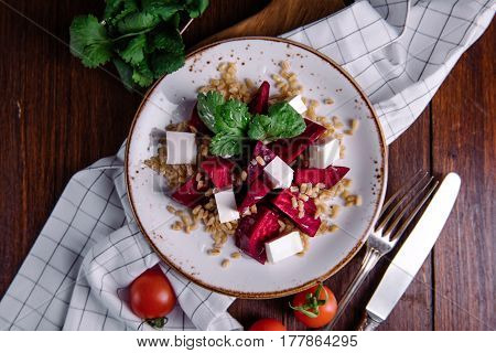 Healthy salad with beetroot, pearl barley, cilantro and brynza cheese on white plate over wooden background, top view, horizontal composition