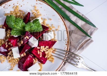 Healthy salad with beetroot, pearl barley, cilantro and brynza cheese on white plate over light grey background, top view, horizontal composition