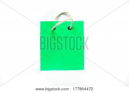 Tiny shopping bag of green paper with rope handles. Isolated over white