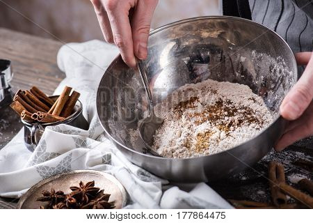 Human hands mixing Ingredients for making cookies with spoon in metal bowl, horizontal composition