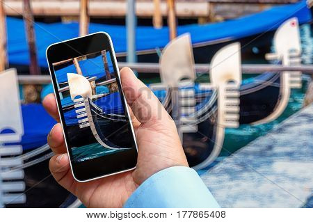 Man Taking A Closeup Picture Of A Gondola With His Smartphone In Hand
