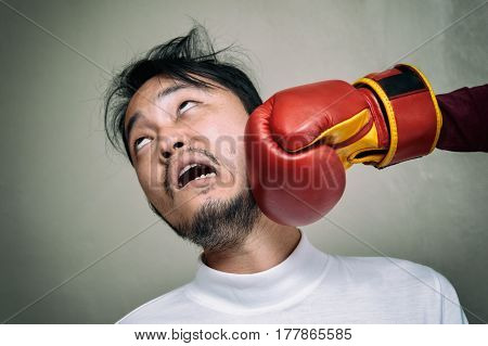 Funny Face Man Getting Punch In Face With Boxing Glove Against Gray Background