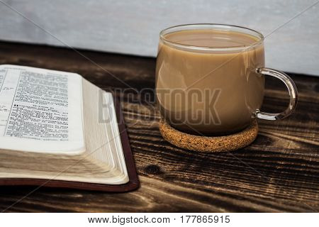 a bible and coffee with milk on wooden background