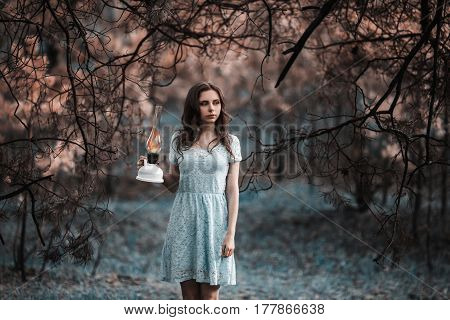 Very cute young mystical girl with a kerosene lamp. Doll appearance. Woman with brown hair in a turquoise dress on nature. Long hair. Natural light. Model posing on the nature. Lamp in hand. Lost in mystical forest