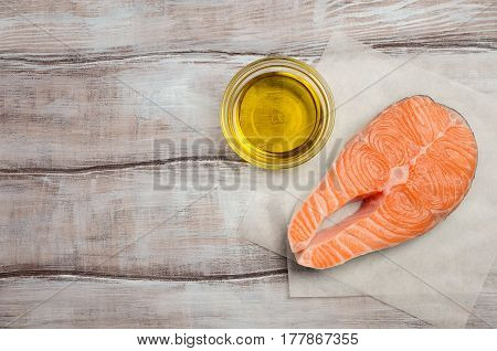 Fresh raw salmon steak with olive oil, ready for cooking. Healthy diet concept. Top view, copy space.