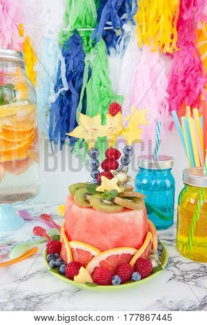Colorful cake made from fresh fruits with party decorations