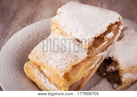 Detail Of Two Slices Of Apple Strudel With Powder Sugar On White Saucer