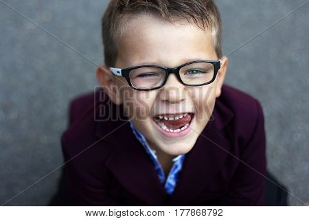 Funny and mischievous first-class boy in glasses and claret jacket shows tongue and winks close-up portrait schoolboy