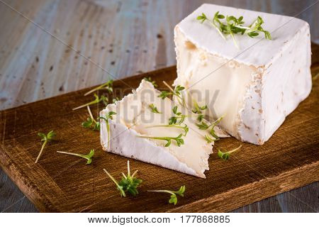Unusual Camembert Cheese With Cube Shape And Spilled Green Cress On Wooden Board