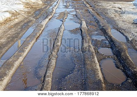 Melting ice on the country road with pot-holes early spring time