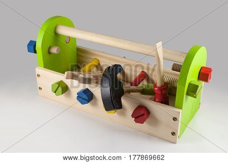 Colorful wooden tool toy set with case and nuts and bolts, isolated studio shot on gradient grey background