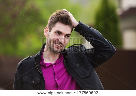 Young attractive cheerful man with dark hair with a beard wearing a shirt and a black jacket on the street. Male street style. Nature in spring. Walking around the city. Cheerful boy
