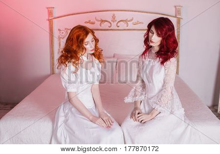 Two beautiful  elegant girls with red hair in a beautiful white wedding victorian  elegant dresses. Female style. The fragile girl. Thin waist. Two elegant women sitting in the bedroom on a white bed