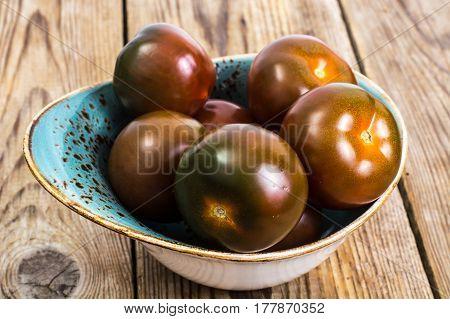 Black tomatoes Kumata on plate. Studio Photo