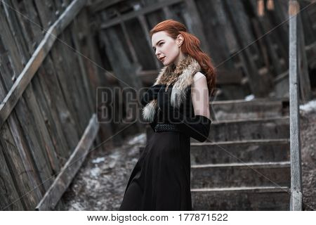 Striking girl with long red hair in black clothes. Woman in black dress and fur around neck with long black gloves posing on background of winter nature. Female street style. Beautiful elegant model