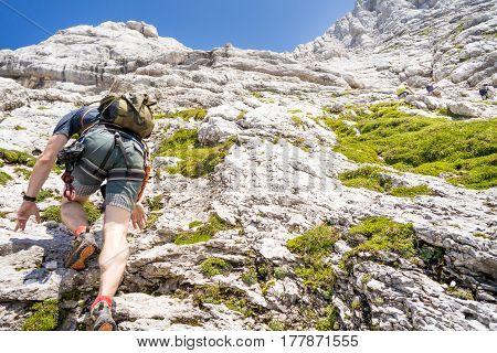 Climber in nature, man climbing mountain, man on via ferrata, summer sports in mountains