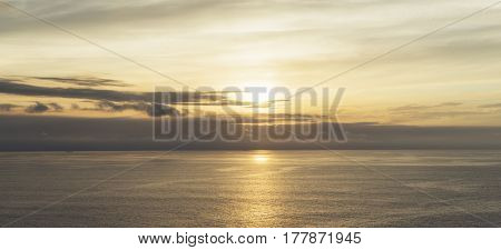 Clouds sky and sunlight gold sunset on horizon ocean. Background seascape dramatic atmosphere rays sunrise. Relax view waves water sea mock up nature evening concept perspective sunrise