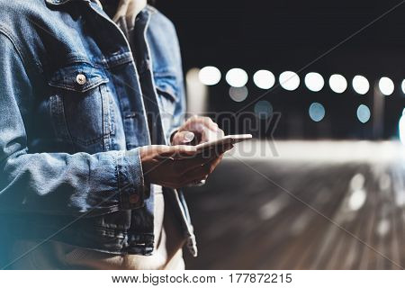 Girl pointing finger on screen smartphone on background illumination bokeh color light in night atmospheric city bridge hipster using in female hands and texting mobile phone mockup glitter street lifestyle
