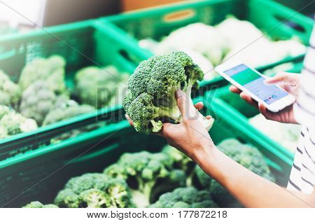 Young woman shopping healthy food in supermarket blur background. Female hands buy products broccoli using smartphone in store. Hipster at grocery using smartphone. Person comparing price of produce