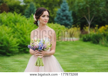 Half-length portrait of a beautiful bride in park. Cute lady with a bouquet in pink wedding dress outdoors. Looking sideways. Grass trees and bushes in the background.