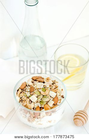 Good morning with homemade granola cereal, nuts, bottle, lemon water, drizzlier for breakfast. Healthy food, Diet, Detox, Clean Eating or Vegetarian concept.