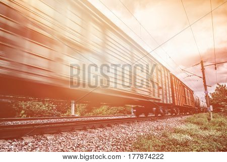 Freight train, railway wagons with motion blur effect. Transportation, railroad, toned image with sun light filter, copy space