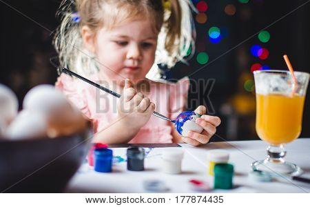 little girl is painting eggs for Easter