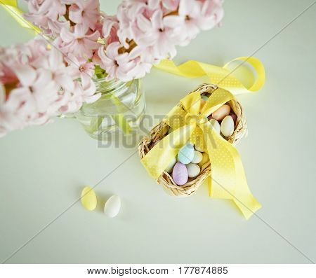 Treat candy for Easter in basket with an yellow bow and glass vase with hyacinths on white table. Empty copy space for text
