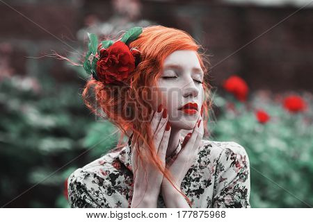 A young woman with red curly hair in a floral dress on a background of a bush with red roses. Red-haired young girl with pale skin blue eyes bright unusual appearance and red lips and thin waist in the garden. Young model