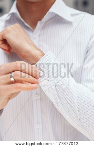 Man buttons cuff-link on French cuffs sleeves luxury white shirt. Close up of a businessman showing a shirt cuff.