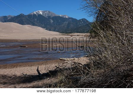 Winter melt off waters of the Medan Creek flows through the Great Sand Dunes National Park in spring time near Alamosa, Colorado