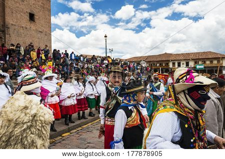 Cuzco Peru - December 25 2013: People wearing traditional clothes and masks dancing the Huaylia in the Christmas day in front of the Cuzco Cathedral in Cuzco Peru.