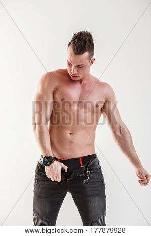 Sexy muscular man body posing at white wall, black jeans