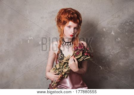 A woman with red hair in a nightgown. Red-haired girl with pale skin and blue eyes with bright unusual appearance with choker around her neck with a bouquet of dried roses. French courtesan in nightgown. Copyspace