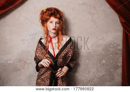 A beautiful woman with red hair in leopard print gown with glasses in hand. Red-haired beautiful girl with pale skin and blue eyes with a bright unusual appearance with a red ribbon around her neck. French beautiful courtesan. Beautiful model