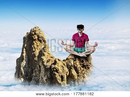 The man in glasses virtual reality sitting in the Lotus position on a rock in the sky