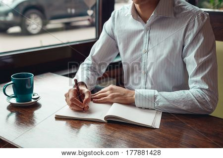 Full concentration man with coffee. Close-up part of young businessman writing in notebook while sitting at his working place outdoor.