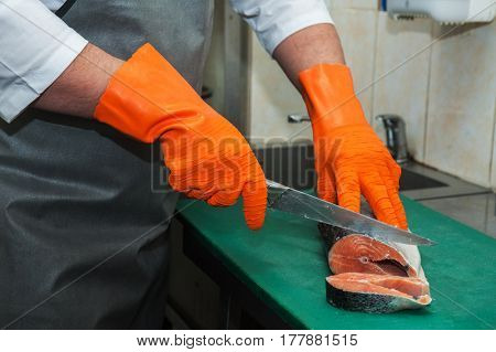 Chef cutting salmon fish on steaks with knife