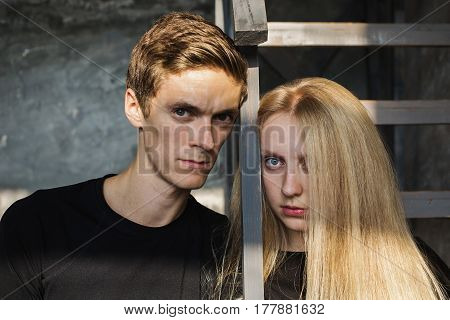 A young man with cheekbones and young blonde woman with long hair. Problems and difficulties in relations. The difficult situation in life. Conceptual photography. Actor play. Hard shadows. Woman and man portrait. Cheekbones on face