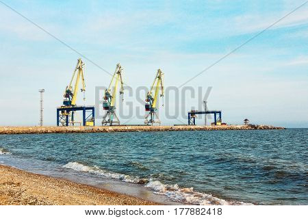 Three dock cranes in seaport against of the blue sky and coastline.