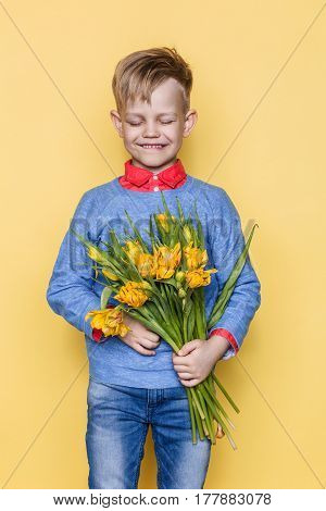 Little beautiful child with a bouquet of tulips. Son gives mom flowers on Women's Day, Mother's Day. Birthday. Valentine's day. Spring. Studio portrait over yellow background