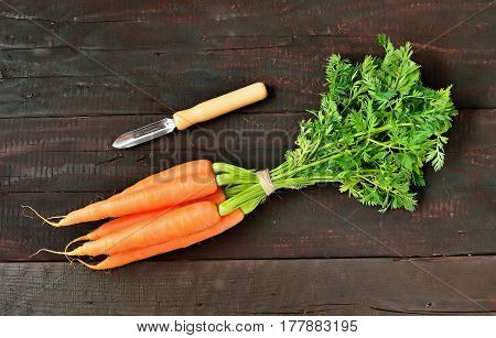 Fresh carrot packet and scraper on wood table background. Tasty and health product. Root vegetable