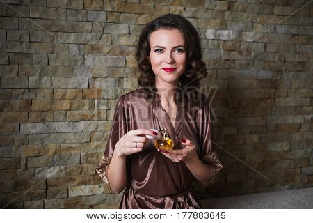 Lovely girl PinUp with brunette hair and retro make-up with red lips in a bathrobe on a dark background. lovely girl sitting on the bed. Vintage image. Lovely woman with perfume bottle